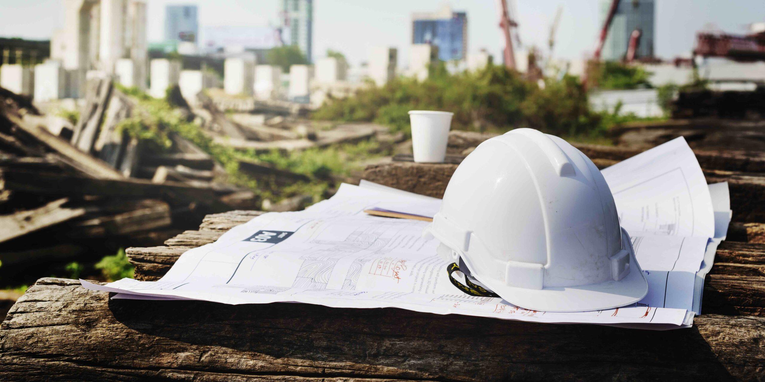 Billede af byggeplads med hjelm og tegninger